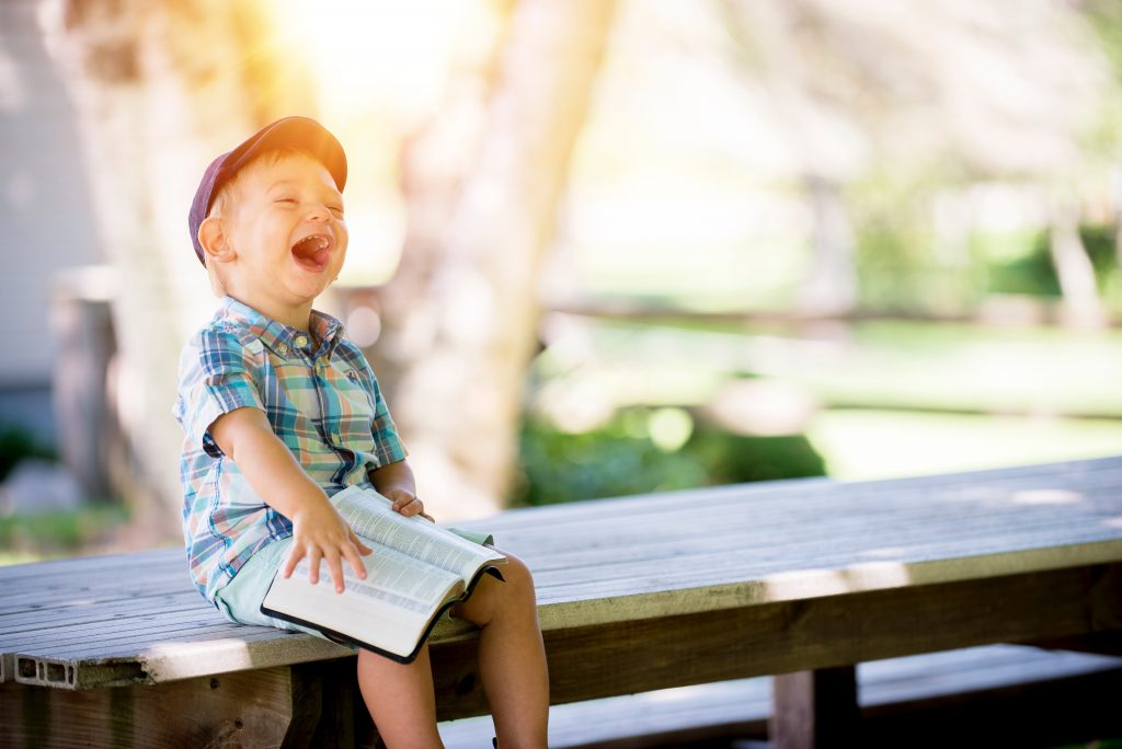 Boy holding book and laughing while sitting on a bench